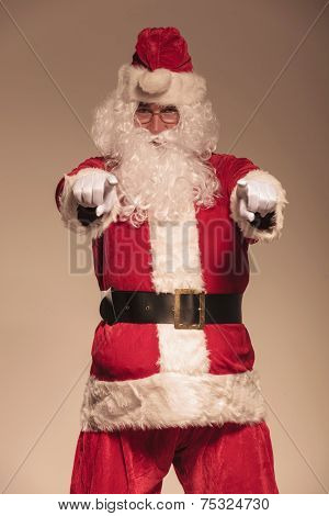 Portrait of Santa Claus pointing at the camera, in studio
