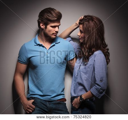In love couple looking at each other, the woman is leaning on her lover while he is holding her with his left hand.