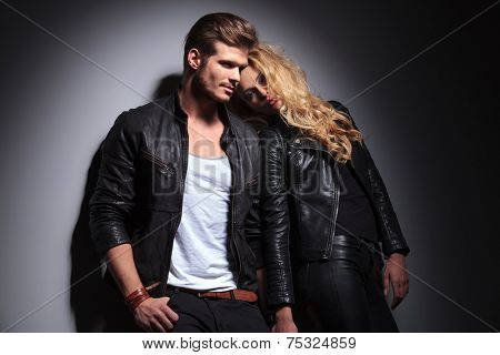 Blonde fashion woman leaning on her lover while he is looking away from the camera, holding his thumb in pocket.
