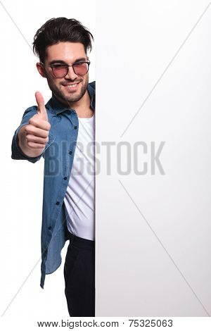 Young casual man presenting a white board while showing the thums up gesture.