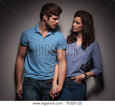 In love fashion couple looking at each other while holding hands, leaning on a grey wall.