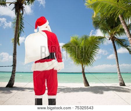 christmas, holidays and people concept - man in costume of santa claus with bag from back over tropical beach background