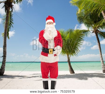 christmas, holidays and people concept - man in costume of santa claus making hush gesture over tropical beach background