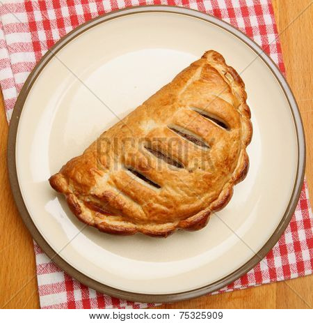Cornish pasty on a beige plate