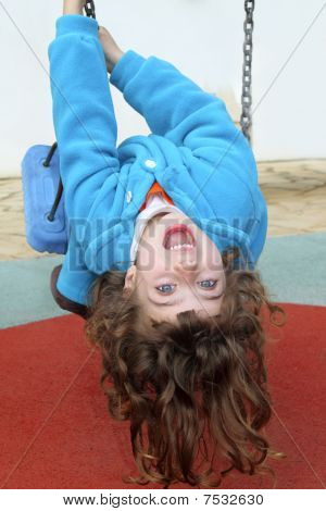 Little Girl Upside Down On Park Playground Swing