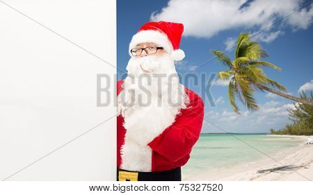 christmas, holidays, advertisement, travel and people concept - man in costume of santa claus with white blank billboard making hust gesture over tropical beach background