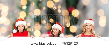 christmas, x-mas, people, advertisement and sale concept - happy women in santa helper hat with blank white board over tree lights background