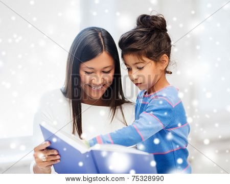 childhood, education, family and people concept - smiling little girl and mother or teacher with book indoors