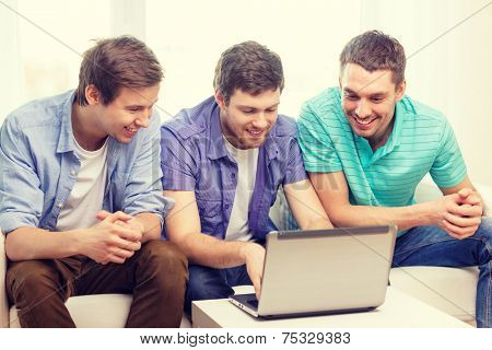 friendship, technology and home concept - smiling male friends with laptop computer at home