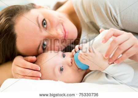 mom feeding baby boy with a milk bottle