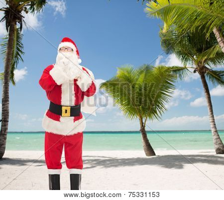 christmas, holidays and people concept - man in costume of santa claus with bag making hush gesture over tropical beach background