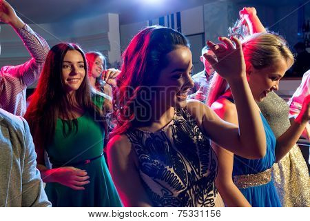 party, holidays, celebration, nightlife and people concept - smiling friends dancing in club