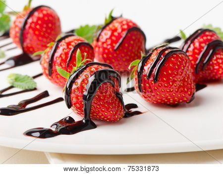 Fresh Strawberries Dipped In Chocolate Sauce On White Plate.
