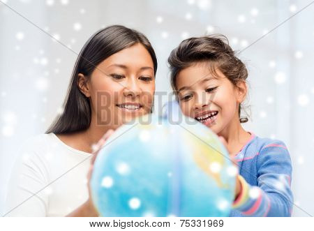 childhood, education, family and people concept - smiling little girl and mother or teacher with globe indoors