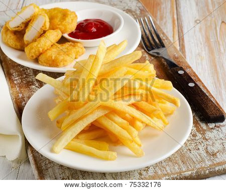 Fries And Chicken Nuggets On   Wooden Table