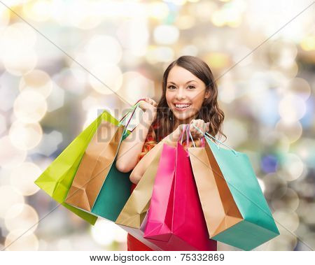 sale, gifts, christmas, holidays and people concept - smiling woman with colorful shopping bags over lights background