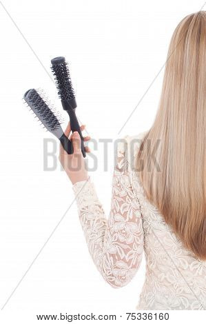 Woman On White Background Holding Brushes And A Hairdryer. Stock Image.