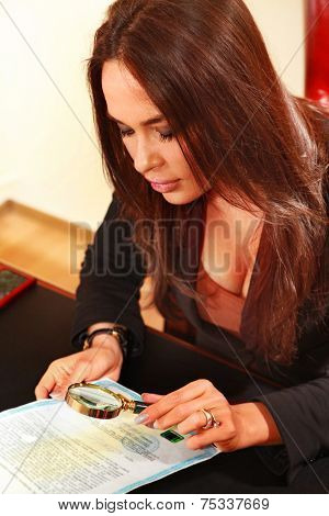 woman reads the document by means of a magnifying glass