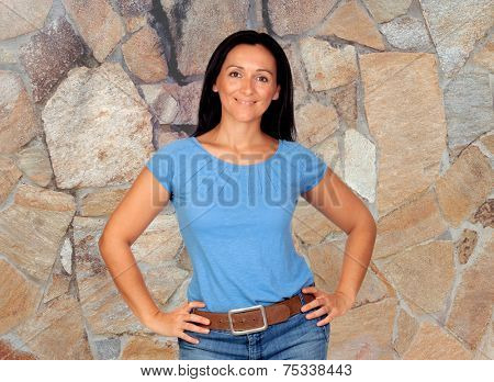 Smiling brunette woman  with a stone wall background