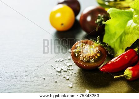 Fresh grape tomatoes with salade leaves and salt for use as cooking ingredients with a halved tomato in the foreground with copyspace