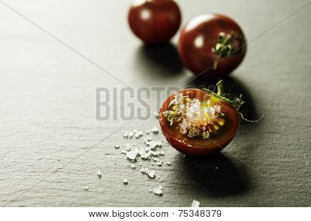 Fresh grape tomatoes with  salt for use as cooking ingredients with a halved tomato in the foreground with copyspace