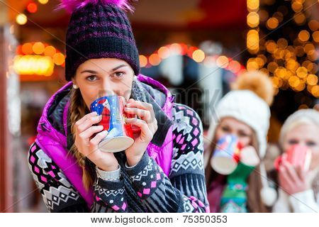 Woman drinking mulled wine in mug on German Christmas Market