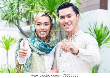 Asian Muslim man and woman moving into house presenting latchkey or key
