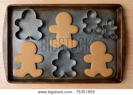 High angle shot of an old baking sheet with Christmas gingerbread man cookies and cookie cutters. Horizontal format on wood kitchen table.