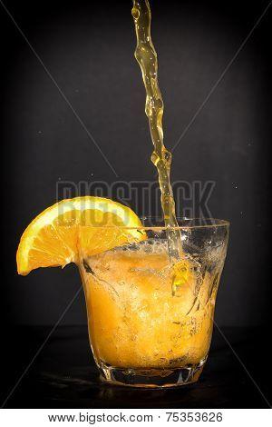 Orange flavoured soft drink splashing over the glass.