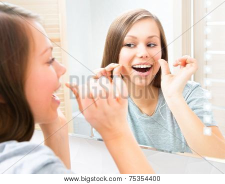 Beauty young woman flossing her teeth at home. Pretty teenage girl using an interdental brush smiling at the mirror enjoying beautiful white teeth. Healthcare of mouth and dental floss. Dental hygiene