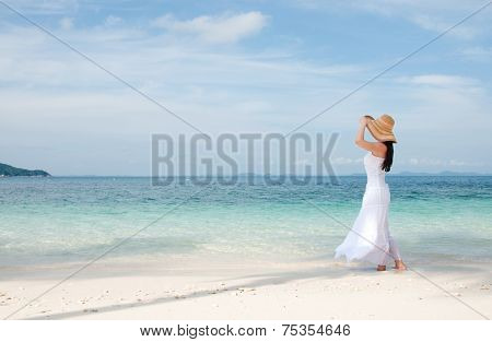 Woman in hat on shoreline at the tropical beach