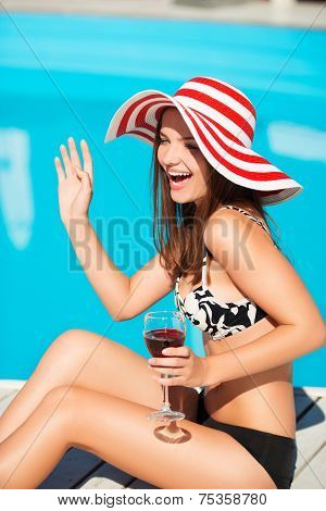 Happy young woman waffing and sitting close by swimming pool