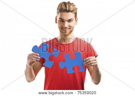 Good looking young man holding a blue puzzle piece, isolated on a white background