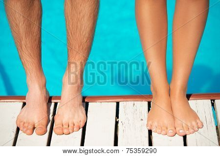 Close-up of beautiful woman and man legs near by swimming pool