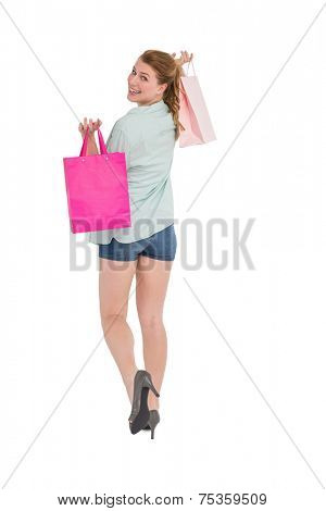 Woman carrying shopping bags over her shoulder on white background