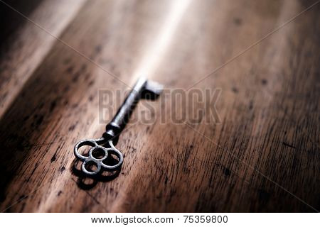 An vintage key on an grungy old desk with a beam of light coming in.