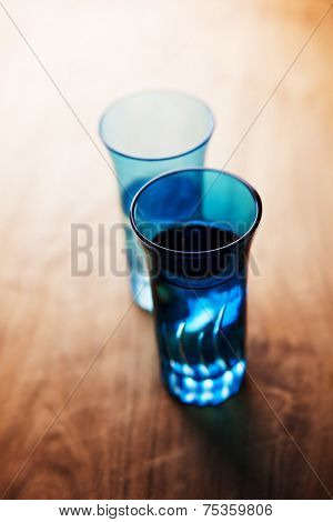Blue glass with drink on a dim counter, with directional light.