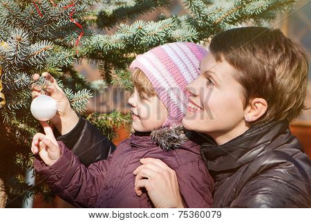 happy mather and daughter decorating New Year tree with toy balls in park