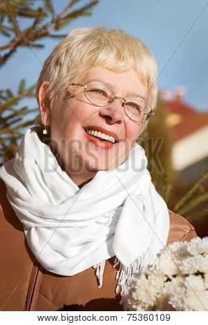 Senior woman portrait, outdoor in front of house