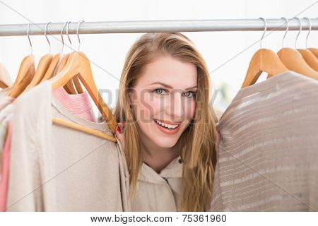 Pretty blonde smiling at camera by clothes rail in the store