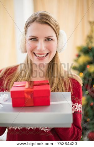 Smiling blonde wearing earmuffs while holding gifts at home in the living room