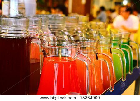 A Row Of Colorful  Juices Served in Jug