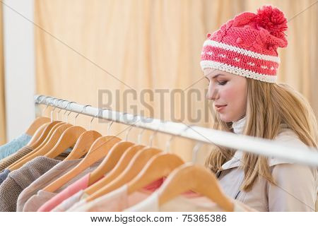 Close up of a pretty blonde looking at clothes on rail in the store