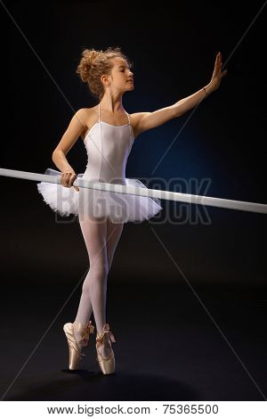 Young ballet student practicing classical ballet in classroom by ballet bar.