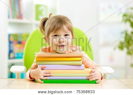 Cute kid girl preschooler with books