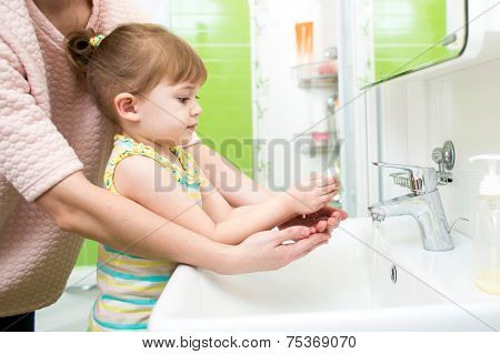 child girl washing hands with soap in bathroom