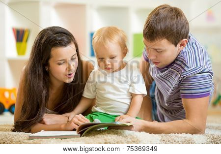 Young happy family with baby boy reading children book