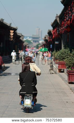women on moped in old town of Pingyao