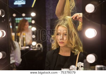 MOSCOW - OCTOBER 25: Beautiful girl with blond wavy hair by hairdresser during Mercedes-Benz Fashion Week Russia on October 25, 2014 in Moscow, Russia.