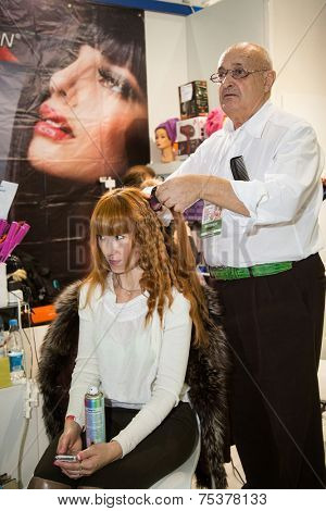 MOSCOW - OCTOBER 24: Hairstylist performs hair colouring at the international exhibition of professional cosmetics and beauty salon equipment INTERCHARM on October 24, 2014 in Moscow